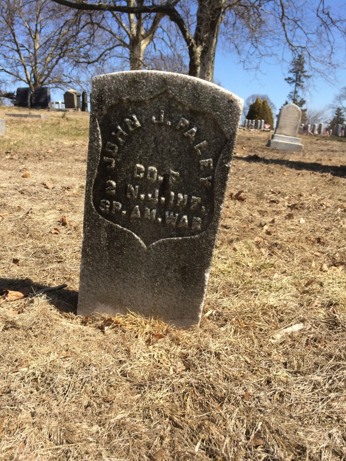 A Spanish-American War headstone tilts on a hillside in Brooklyn's Green-Wood Cemetery