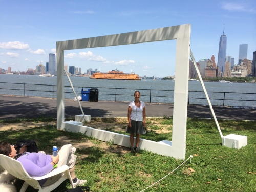 Artist D. Chase Angier in front of her creation. The orange boat is the Staten Island Ferry sailing by.