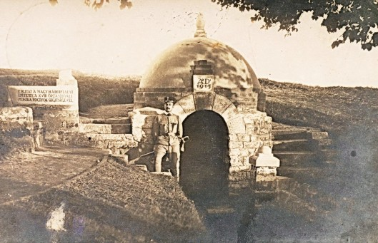 "The well at Kissitke POW camp, Hungary, in 1915. The inscription on the left reads: ""This well was built in the Great War by the 18th guard battalion with the help of Russian prisoners."" Béla Zombory-Moldován, camp commandant and well-creator, wears the ""wretched"" regulation officer's sword that had been the bane of his life at the front."
