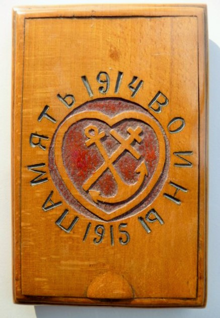"Cigarette-case in beechwood by an unknown Russian POW, 1915. The words in Cyrillic mean ""In memory of the soldiers"". The cross stands for faith, the anchor for hope, and the encircling heart for love, the greatest of the Christian virtues. Instead of the Russian cross with its three crossbars, the carver has used a two-barred form known as the Patriarchal cross, which may indicate that he was from Belarus. The cross on the Hungarian coat of arms has two bars of nearly equal length."