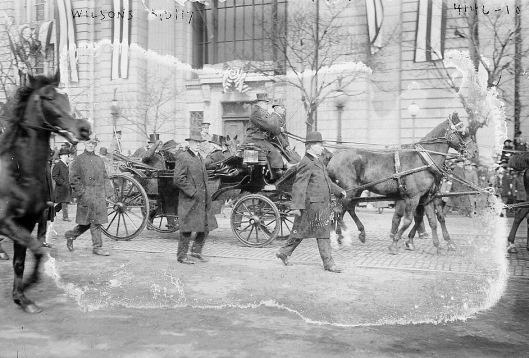 This grainy image captures the cold and grim mood in Washington as President Wilson (top hat, in carriage) attends the ceremony for his second inaugural on 5 March 1917.